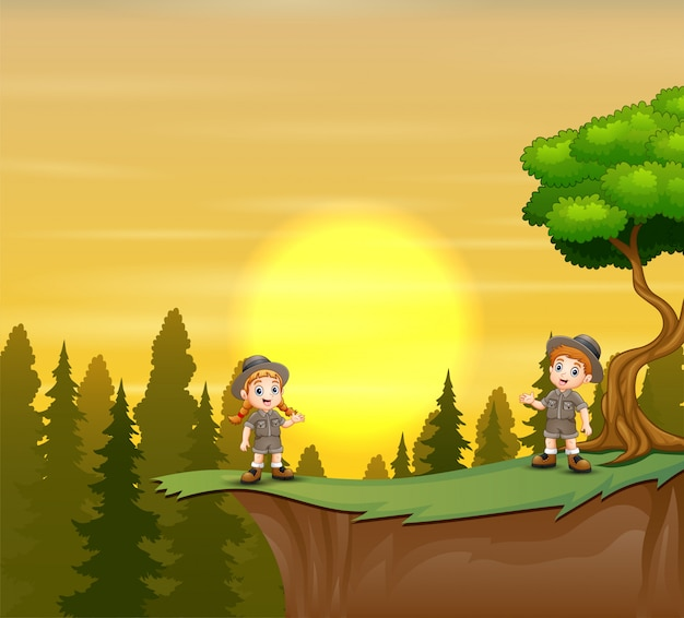 Scout boy and girl standing on mountain cliff of sunset