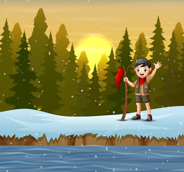 A scout boy with red flag on winter landscape