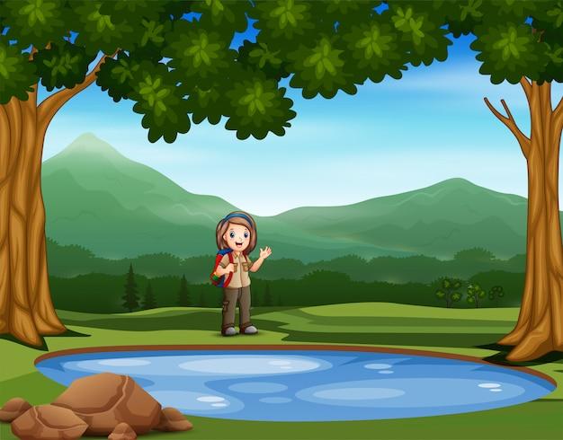 Скаутская девушка отдыхает возле маленького пруда