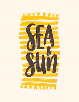 Sea and sun slogan handwritten with elegant cursive font on beach towel or blanket.