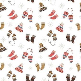 Бесшовный рождественский образец с уютными и теплыми носками, шапками и варежками