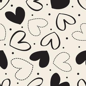 シームレスなモノクロバレンタインのパターンの背景に描かれた心とポルカドット