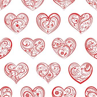 白地に赤のカール、花、葉の飾りと大きなハートのシームレスなパターン