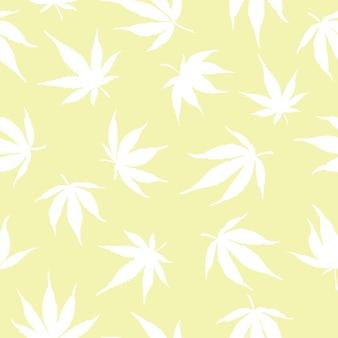 黄色の背景に白い大麻の葉のシームレスなパターン