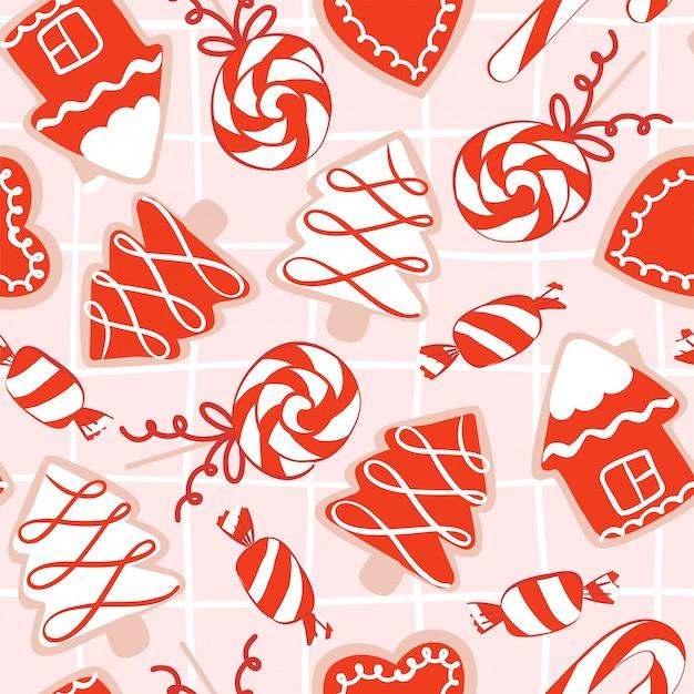 Бесшовный фон с рождественским рисованным печеньем с сахарной глазурью красного, розового и белого цветов в форме домика, рождественской елки, орнамента, носков, конфет и чашки с какао