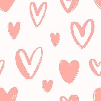 白い背景の上の手描きのピンクのハートとシームレスなパターン