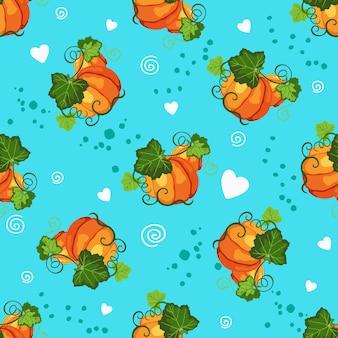 オレンジ色の熟したカボチャ、緑の葉と青い背景の装飾的なハートとのシームレスなパターン