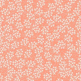 白い花とオレンジ色の背景とのシームレスなパターン