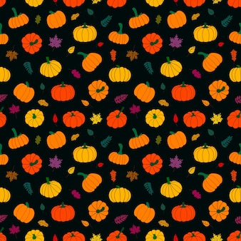 Seamless pattern of withered leaves and ripe pumpkins on a dark background