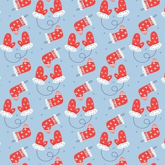 クリスマスのミトンと靴下のシームレスなベクトルパターン。クリスマスプレゼントの青い背景