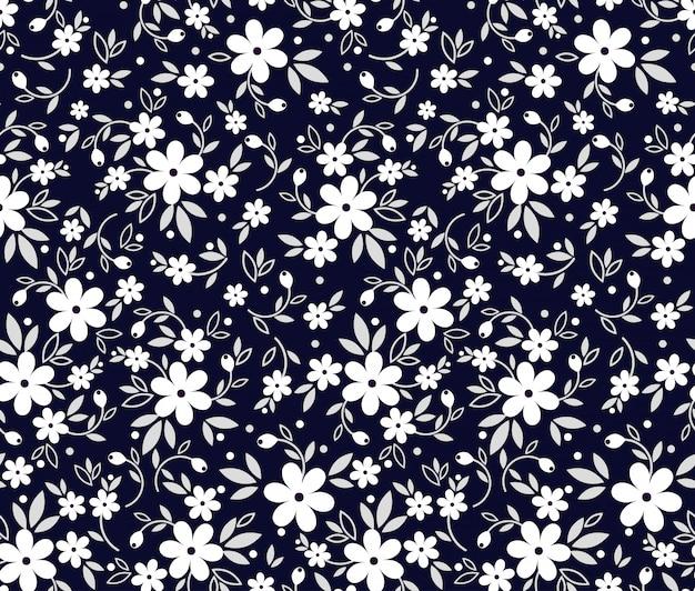 シームレスなヴィンテージ花柄。濃い青色の背景、小さな白い花。頭が変なモチーフの黒と白のベクトルプリント。表面のトレンディなデザイン。
