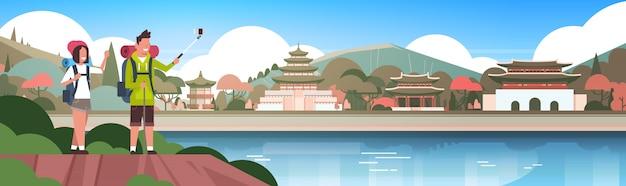 バックパックを持つ観光客のカップルは美しい中国の建物の背景の上にselfieを取るアジアで水平方向のバナーで男女ハイカー