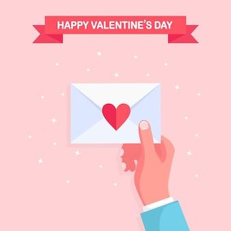 送信、ラブレターの受信、郵便によるメッセージ幸せなバレンタインデー赤いハートの封筒を手に