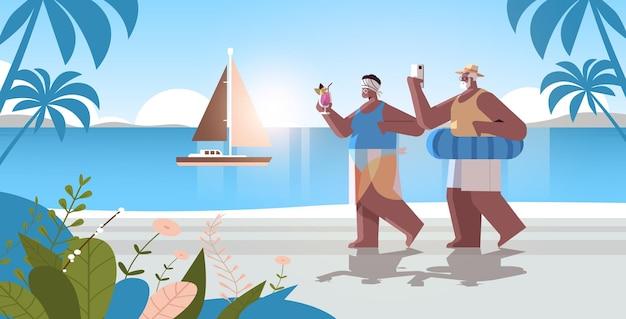 楽しんでいる熱帯のビーチの祖父母でカクテルを飲み、スマートフォンを使用してシニアアフリカ系アメリカ人のカップル