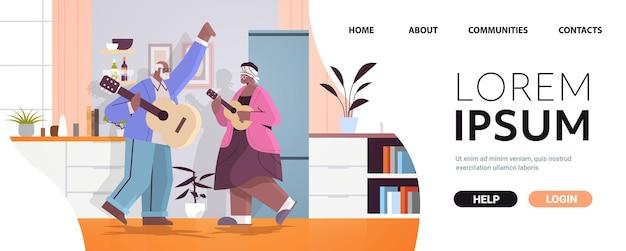기타 조부모를 연주하는 수석 아프리카계 미국인 부부는 즐거운 노년 컨셉의 거실 인테리어를 즐기고 있습니다.