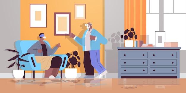 가상 현실 대화형 서비스 활성 노년 개념 거실 내부 수평 전체 길이 vect를 탐색하는 디지털 안경에 vr 헤드셋 조부모를 착용 한 수석 아프리카 계 미국인 부부