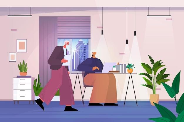 현대 사무실에서 일하는 디지털 가제트 비즈니스 사람들을 사용하는 수석 사업가 커플