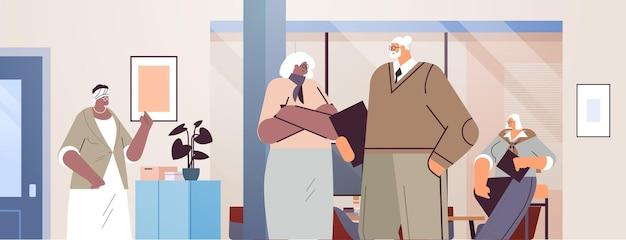 노년에 함께 일하는 공식적인 옷을 입은 사업가들을 만나는 동안 토론하는 고위 기업인 팀