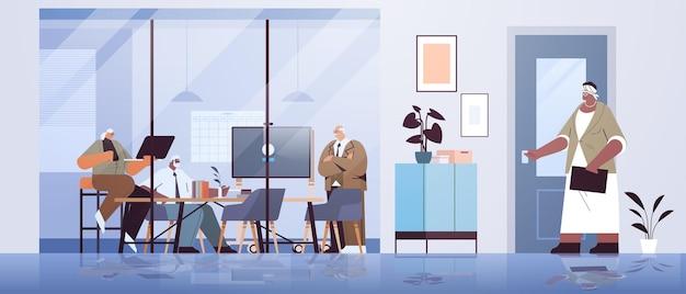 사무실에서 함께 일하는 정장 차림의 혼합 인종 사업가들이 회의 중에 토론하는 고위 기업인 팀