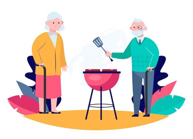 Пожилая пара готовит барбекю мясо в саду