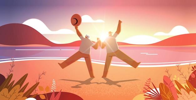 老人と女性のアクティブな老後の概念海景夕日の背景を楽しんで踊る老夫婦
