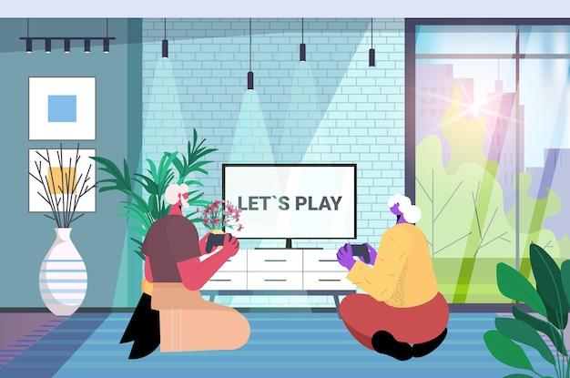 무선 게임 패드 컨트롤러를 사용하여 비디오 게임을 하는 조부모와 즐거운 시간을 보내는 노부부