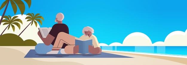 Старшая пара читает книги на пляже, старик и женщина, семья проводят время вместе, отдыхая на пенсии
