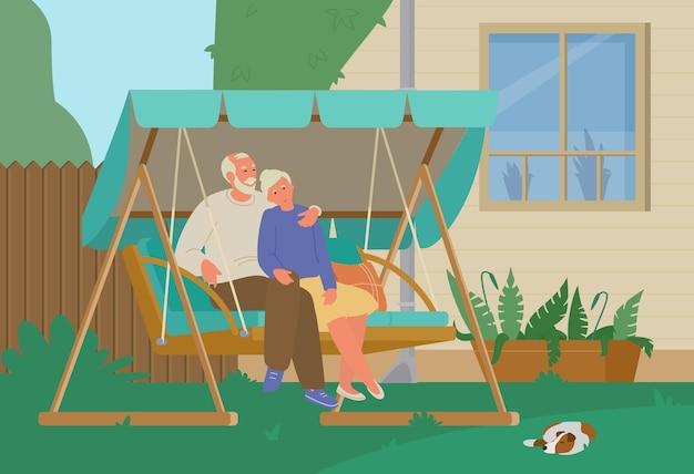 裏庭の庭のブランコで休んでいる年配のカップル