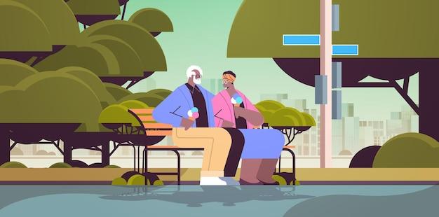 벤치에 앉아 아이스크림을 먹는 노인 부부는 공원에서 함께 시간을 보내는 행복한 아프리카계 미국인 조부모