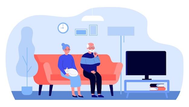 家でテレビを見ている年配のカップル