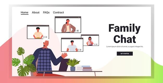 ビデオ通話のオンラインコミュニケーションコンセプトリビングルームインテリアコピースペース中にwebブラウザーのウィンドウで家族と仮想会議を持つシニア男性