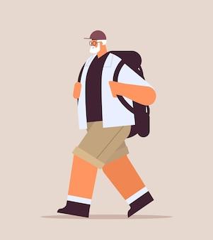 Старший мужчина турист, путешествующий с рюкзаком, концепция физической активности в старости, полная длина