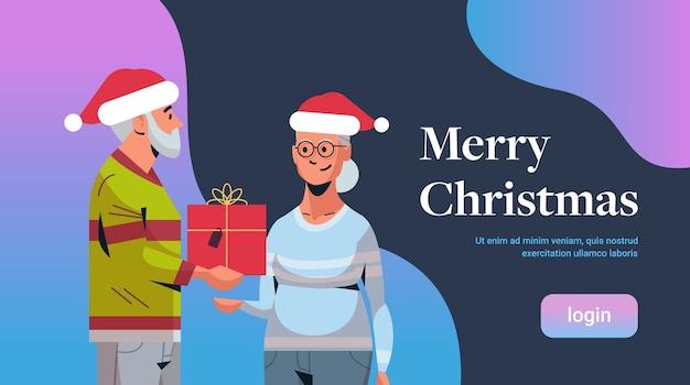 Старший мужчина в новогодней шапке дарит подарочную коробку зрелой женщине семья празднует счастливого рождества с новым годом зимние праздники концепция портрет копировать пространство баннер