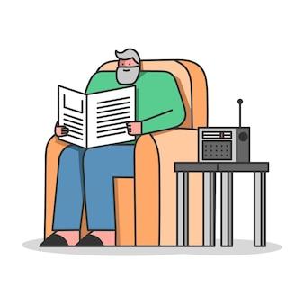 Старший мужчина читает газету, слушает радио, сидя в кресле
