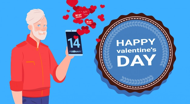 Senior man use smart phone sending happy valentines day congradulations over blue background