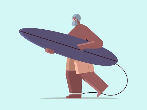 서핑 보드를 가진 시니어 남자는 서핑 보드 여름 휴가 활성 노년 개념을 들고 세 아프리카 계 미국인 서퍼