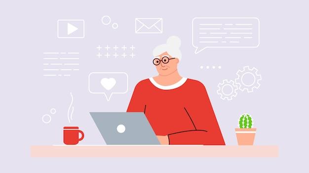 年配の女性は、ラップトップを使用して最新のテクノロジーを研究しています。ポジティブな笑顔の祖母は、コンピューターの前に座って、インターネットでオンラインで通信し、新しいことを学びます。大人が働いています。