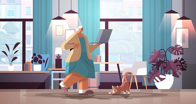 집에서 소셜 미디어 네트워크 개념 거실 인테리어 전체 길이 수평 벡터 일러스트 레이 션에서 휴식 노트북 할머니를 사용 하는 수석 여자
