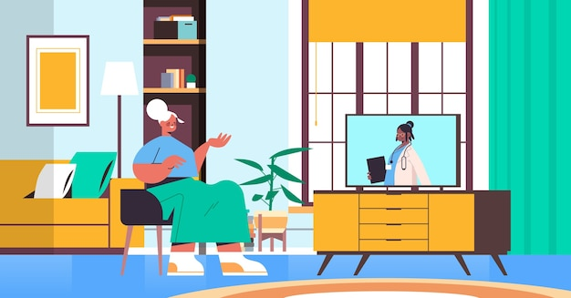 Senior woman watching online video consultation with female doctor on tv screen healthcare telemedicine medical advice concept living room interior horizontal
