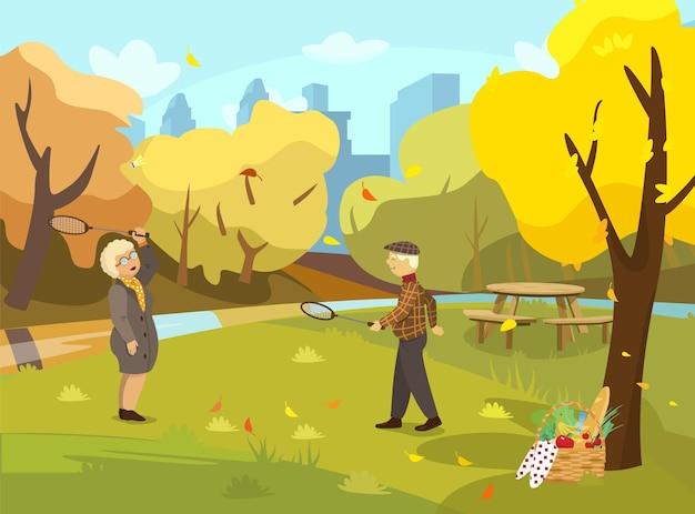 Seniorcouple playing badminton in autumn park fall park scene