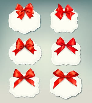 Set of beautiful retro labels with red gift bows with ribbons. Premium Vector