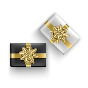 Set of black and white gift boxes with realistic gold ribbon, top view.