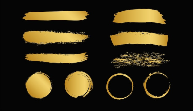 Set of gold paint brush strokes isolated on black background.