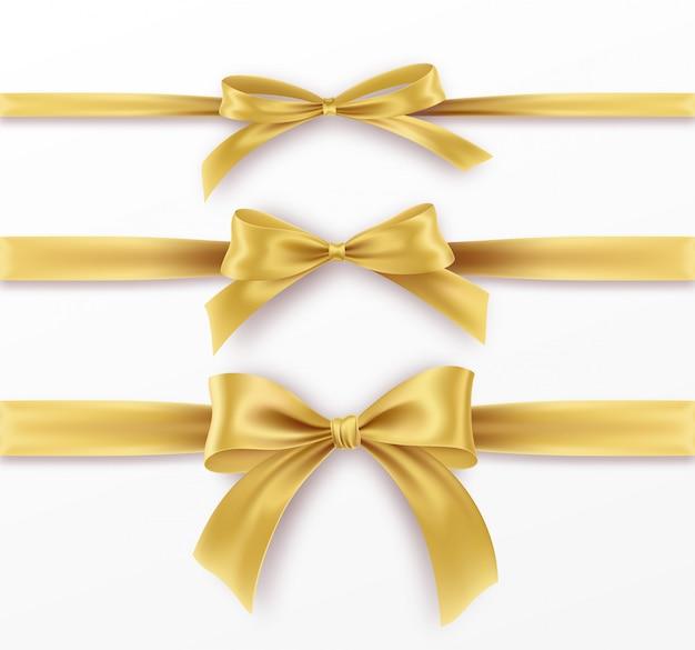 白い背景の上の黄金の弓とリボンを設定します。現実的な金の弓。