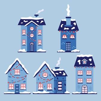 クリスマスの雪に覆われた家のセット。フラットスタイルの青い新年のベクトルの家