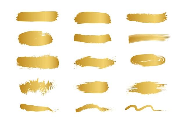 白い背景で隔離の金のペイントブラシストロークのセット