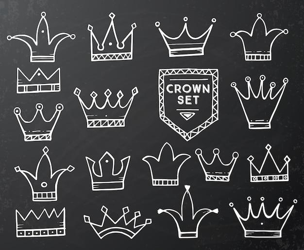 黒の黒板に手描きの漫画の王冠のセットです。ベクトルイラスト。