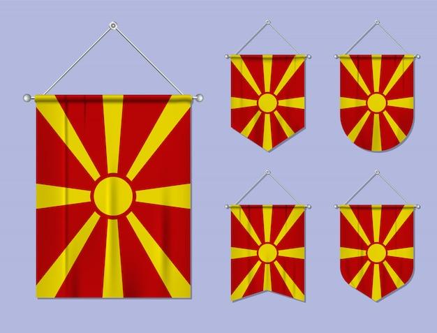 Набор висящих флагов македонии с текстильной текстурой. разнообразие форм национального флага страны. вертикальный шаблон вымпела