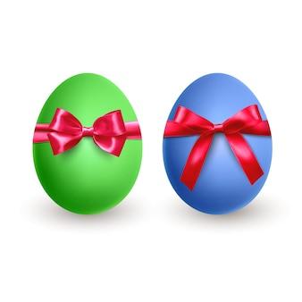 Набор реалистичных зеленых и синих пасхальных яиц с красным бантом