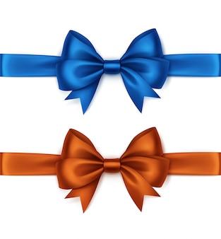 Набор блестящих оранжево-синих атласных бантов и лент вид сверху крупным планом на белом фоне
